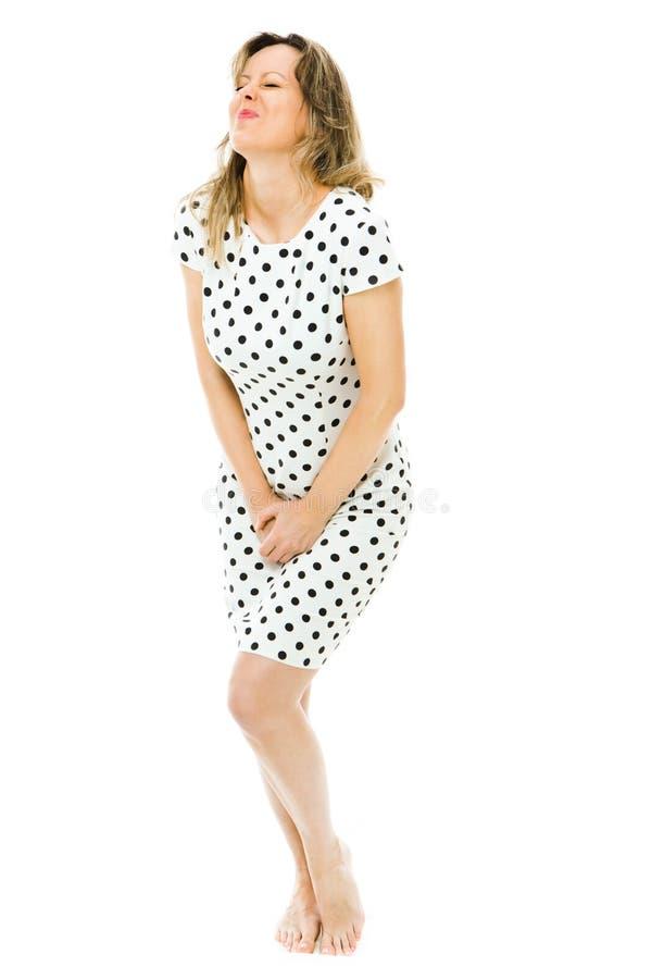 Eine Frau im Kleid des Punktes Bedürfnis dringend Toilette lizenzfreies stockbild
