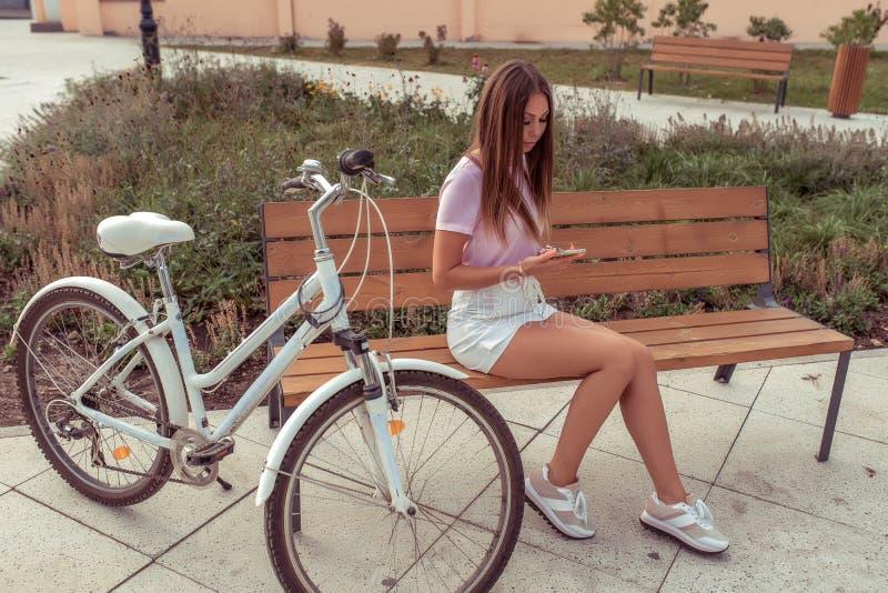 Eine Frau im Sommer sitzt auf einer Stadtparkbank mit einem Fahrrad und hält ein Telefon in ihren Händen On-line-Anruf telefonisc stockfotos