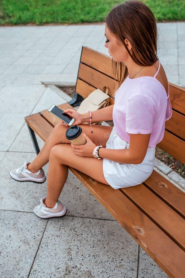 Eine Frau im Sommer sitzt herein auf einer Bank in einem Stadtpark Ein Tasse Kaffee-Tee, on-line-Anruf, Telefon, Mittagessenimbiß stockfotos
