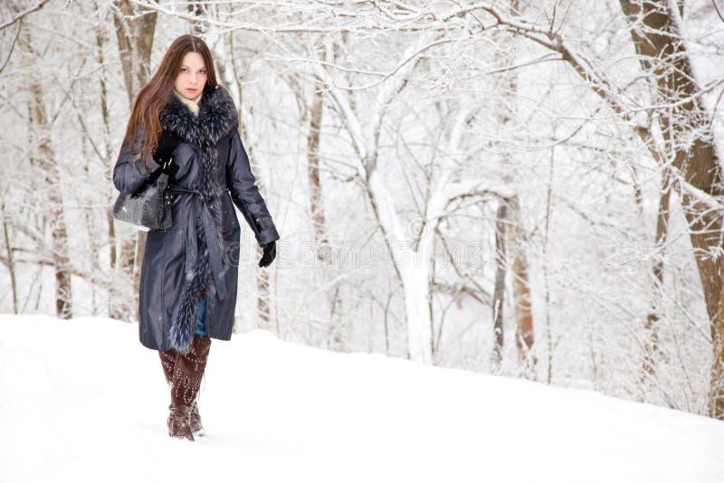 Eine Frau ist im Winterpark lizenzfreie stockbilder