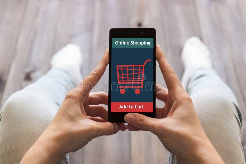 Eine Frau kauft am Online-Shop Warenkorb-Ikone Elektronischer Geschäftsverkehr stockbilder