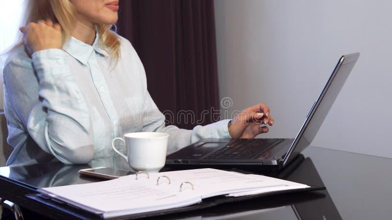 Eine Frau liest wichtige Dokumente in einem Ordner und in den Arten es in einen Laptop stockfoto