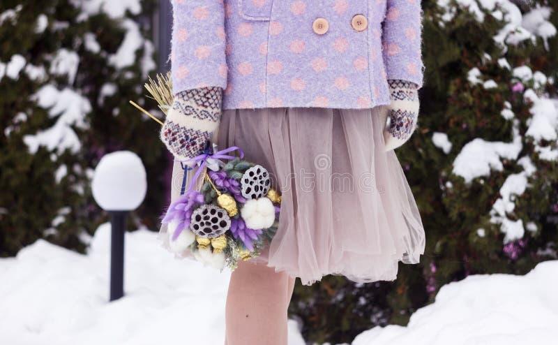 Eine Frau mit dem rosa Haar in einem Mantel und in den Handschuhen ist vom ursprünglichen Blumenstrauß von Trockenblumen lizenzfreies stockbild