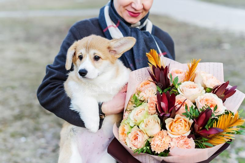 Eine Frau mit einem Hündchen in ihrer Hand Die zweite Hand ist eine Frau, die einen schönen Blumenblumenstrauß hält lizenzfreie stockbilder