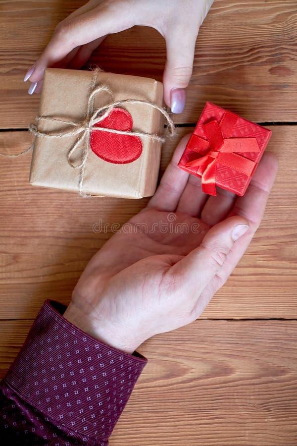 Eine Frau mit einem Mann, der ein Geschenk in seiner Hand auf einem hölzernen Hintergrund am Valentinstag oder am Weihnachten häl lizenzfreie stockbilder