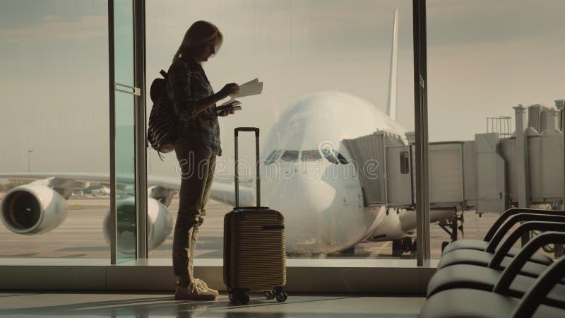 Eine Frau mit einem Pass und einer Bordkarte steht am enormen Fenster, hinter dem Sie das Passagierflugzeug sehen können anfang stockbild