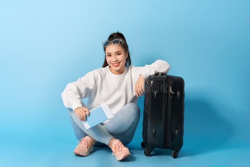Eine Frau mit einem Pass und einer Karte sitzt auf dem Boden nahe einem schwarzen Koffer in der Sonnenbrille stockbild