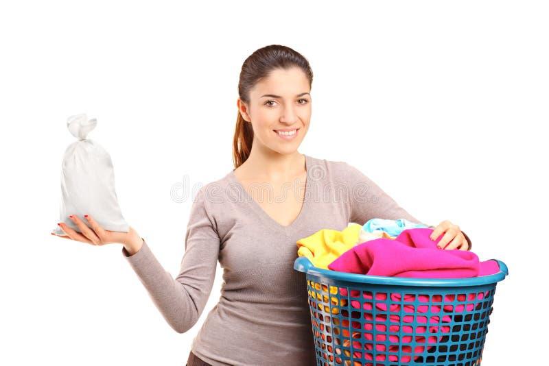 Eine Frau mit einem Wäschereikorb, der einen Geldbeutel anhält stockbilder