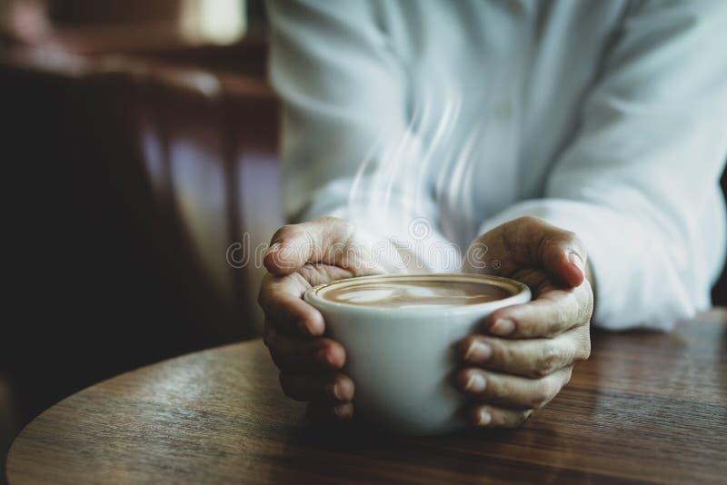 Eine Frau mit einer großen weißen Kaffeetasse lizenzfreie stockfotografie