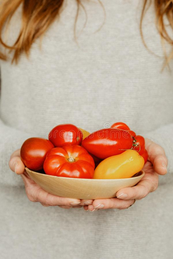 Eine Frau mit einer Schüssel Tomaten und Pfeffern stockbild