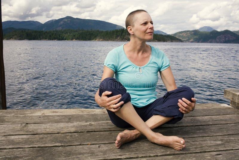 Eine Frau mit Haarausfall von der Chemotherapiebehandlung sitzt draußen auf einem Dock mit dem Ozean und Bergen hinter ihr stockfotografie