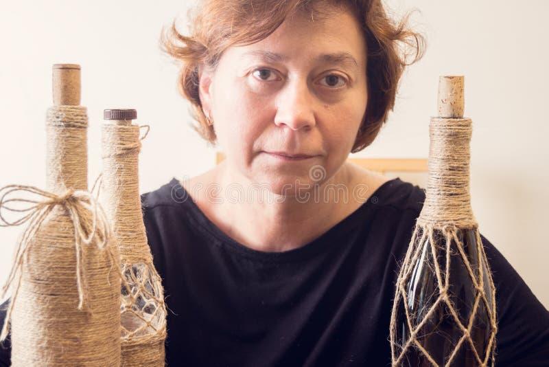 Eine Frau mit ihren handgemachten Flaschen Rustikale Art Geschenke für Weihnachten und andere Feiern In Handarbeit machen des Pro stockbilder