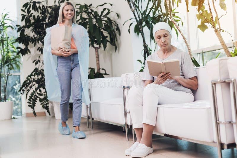 Eine Frau mit Krebs sitzt auf einem weißen Sofa in einer modernen Klinik Ihre Tochter kam, sie zu sehen lizenzfreie stockbilder
