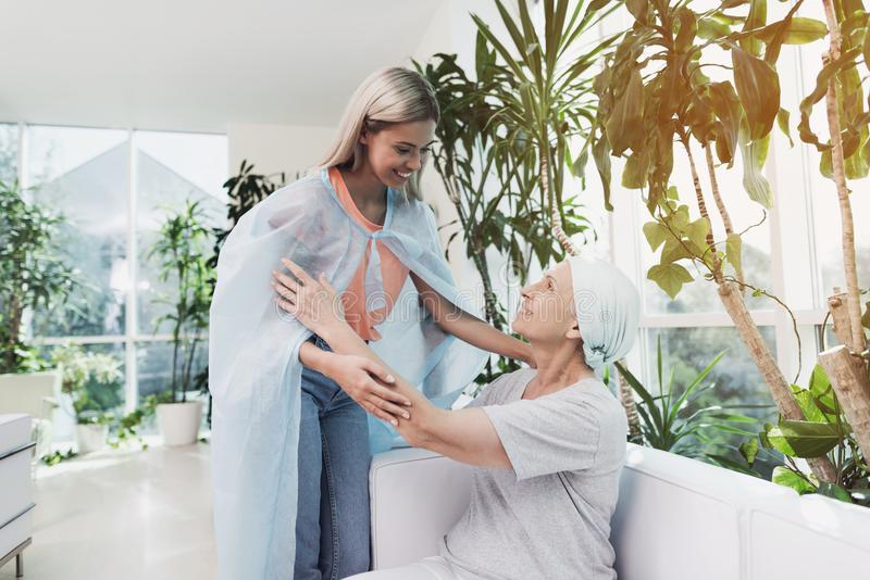 Eine Frau mit Krebs sitzt auf einem weißen Sofa in einer modernen Klinik Ihre Tochter kam, sie zu sehen stockfotografie