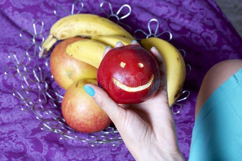 Eine Frau nimmt einen roten Apfel mit einem geschnitzten Emoticon von einem Teller Es gibt einen Obstkorb im Hintergrund Einige Ä lizenzfreie stockfotografie