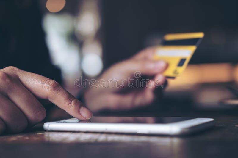 Eine Frau ` s Hand, die Kreditkarte hält und am Handy auf Holztisch im Büro drückt stockfotografie