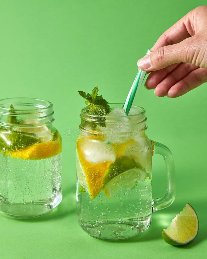 Eine Frau ` s Hand fügt Plastikstrohe in ein Glasgefäß mit Limonade von den natürlichen Bestandteilen - Wasser, Minze, Scheiben v lizenzfreie stockfotos