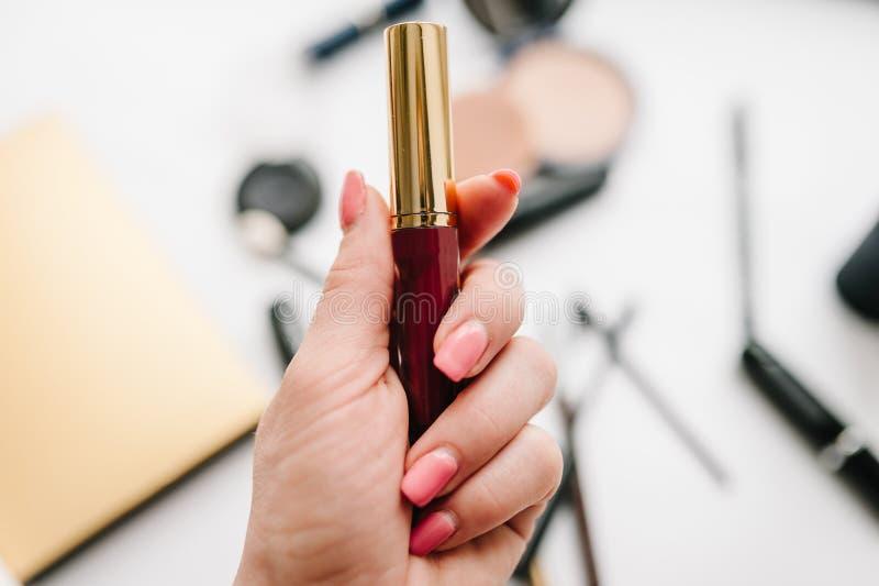 Eine Frau ` s Hand hält Lippenstift oder Lipgloss auf einem undeutlichen stockbilder