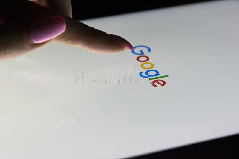 Eine Frau ` s Hand ist Touch Screen auf Tablet-Computer iPad, das nachts für das Suchen auf Google-Suchhomepage Pro ist Google stockfotografie