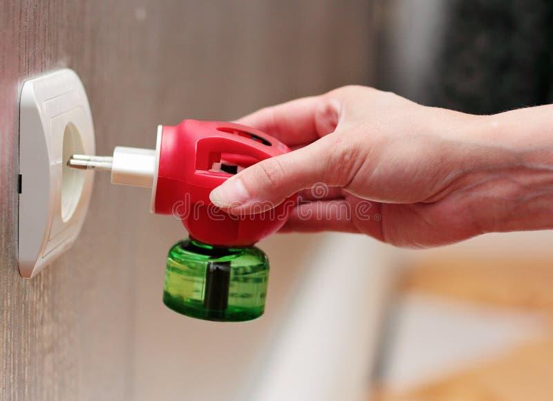 Eine Frau setzt in den Sockel ein Gerät für Schutz gegen insec ein lizenzfreie stockbilder