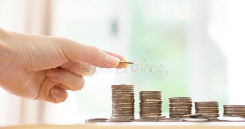 Eine Frau setzte Münzen zum Stapel Münzen stockfoto