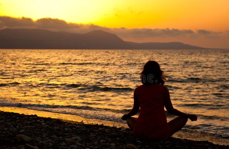Eine Frau sitzt auf dem Strand lizenzfreie stockfotografie