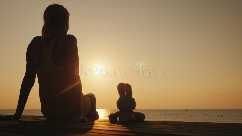 Eine Frau sitzt auf einem Pier nahe bei einem Spielzeughasen Zusammen treffen sie den Sonnenaufgang über dem Meer Romantisches St stockbilder
