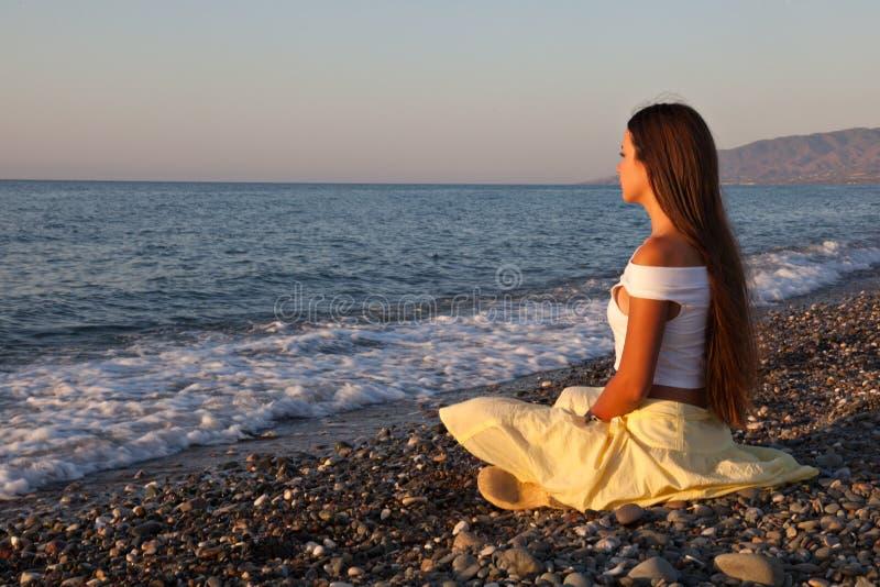 Eine Frau sitzt auf einem Strand stockfotos