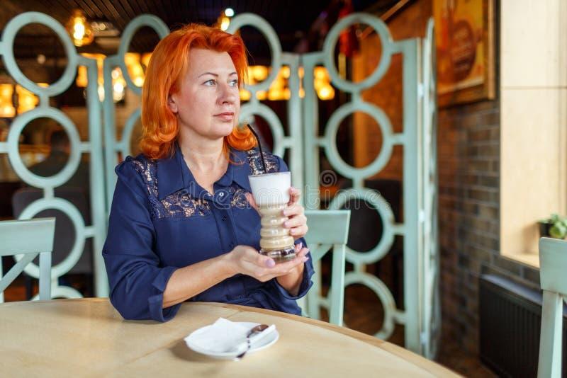 Eine Frau sitzt in einem Café und trinkt ein Kaffeegetränk lizenzfreie stockbilder