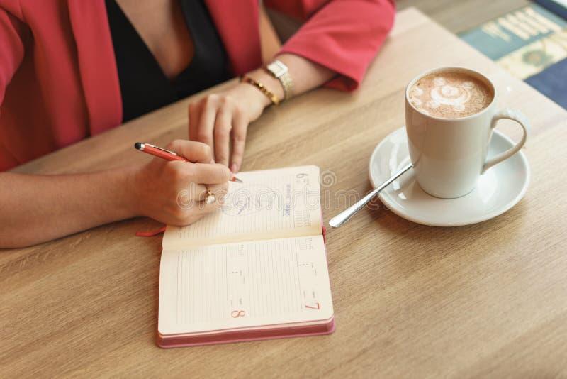 Eine Frau sitzt an einem Tisch in einem Café mit einem Ersatzbuch Steht auf dem Tisch einen Becher Cappuccino Verhandlungskonzept lizenzfreies stockfoto