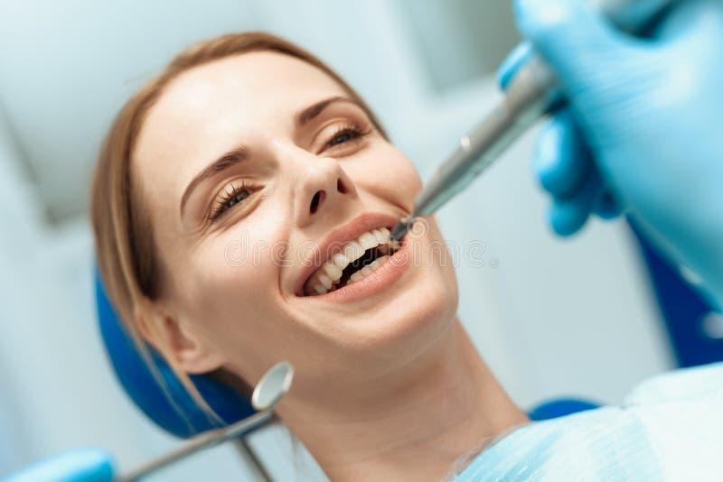 Eine Frau sitzt in einem zahnmedizinischen Stuhl, Doktorzahnärzte, die über sie verbogen werden lizenzfreie stockfotos