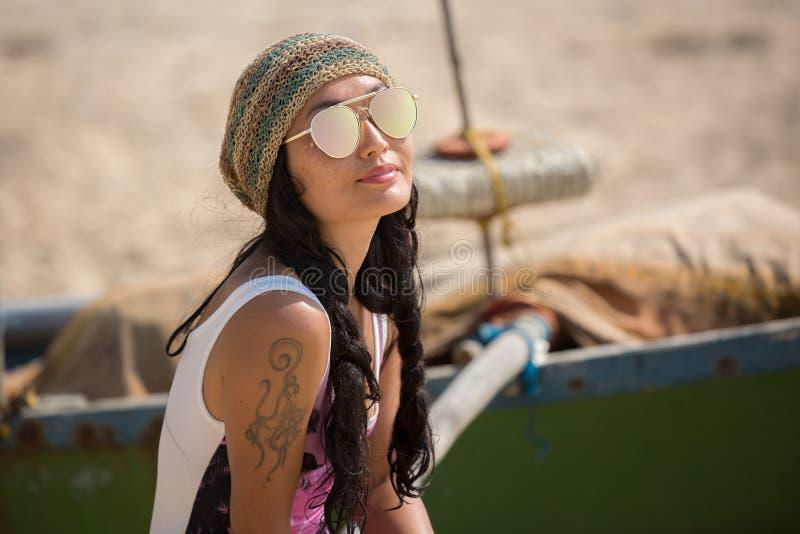 Eine Frau sitzt nahe tragender Sonnenbrille eines Bootes und einem Hut lizenzfreies stockfoto