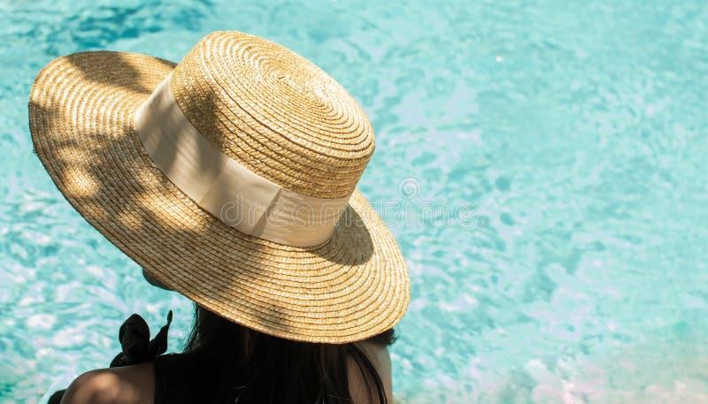 Eine Frau sitzt neben dem Pool lizenzfreie stockfotografie