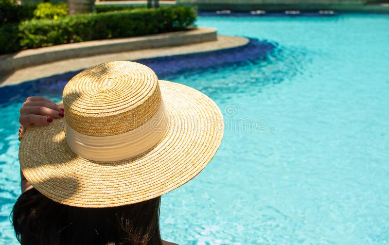 Eine Frau sitzt neben dem Pool lizenzfreies stockbild