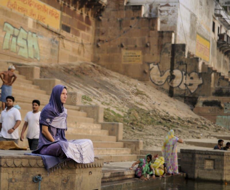 Eine Frau sitzt ruhig im Ganges am frühen Morgen lizenzfreie stockfotos