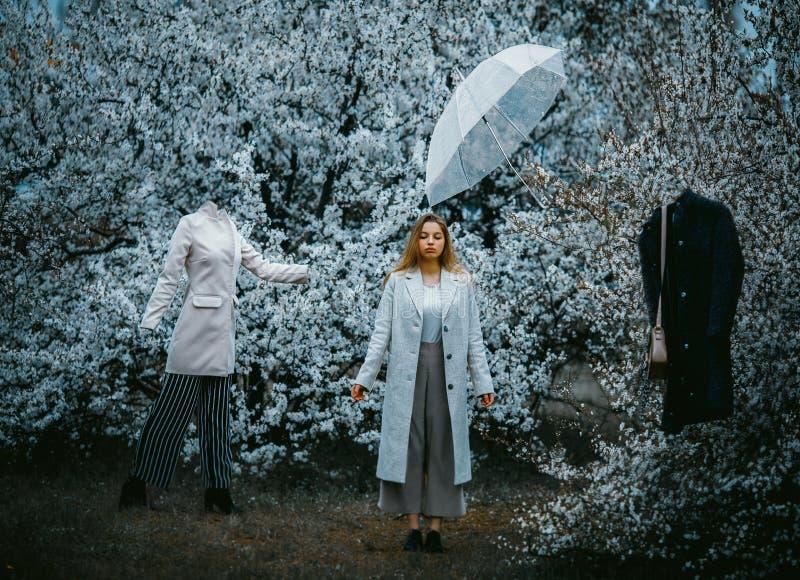 Eine Frau steht in einem blühenden Garten unter Mannequins und einem Regenschirmfliegen in der Luft stockbild