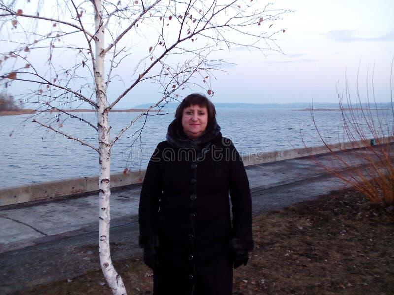 Eine Frau steht nahe der Birke stockfotos