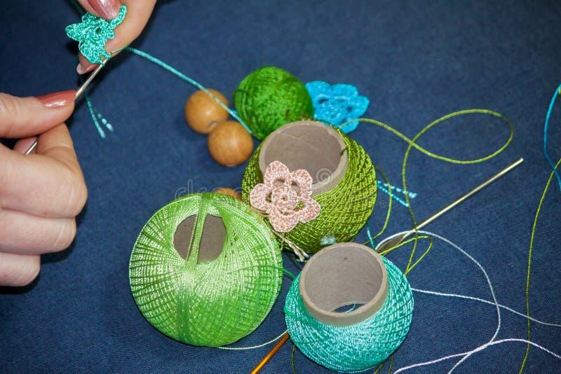 Eine Frau strickt eine Häkelarbeitblume mit blauen Threads, Verwicklungen von mul stockbilder