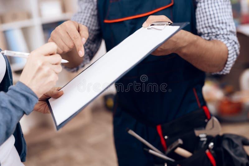 Eine Frau unterzeichnet eine Tat der Arbeit erfolgt von einem Schlosser Der Heimwerker erbringt Dienstleistungen dem Kunden lizenzfreie stockfotografie