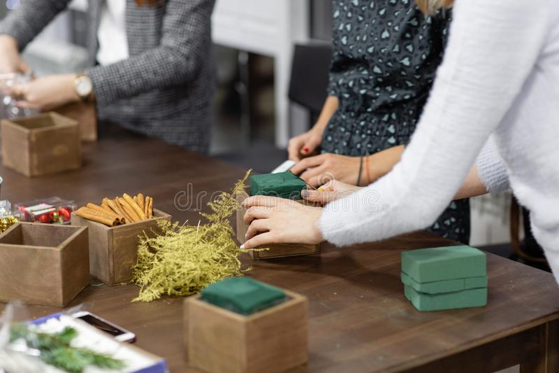 Eine Frau verziert eine Weihnachtsanordnung mit Kerzen Übergibt Nahaufnahme Vorlagenklasse auf der Herstellung von dekorativen Ve stockfotografie