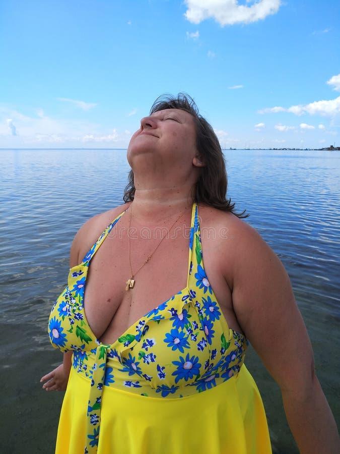 Eine Frau von mittlerem Alter nimmt ein Sonnenbad stockbild