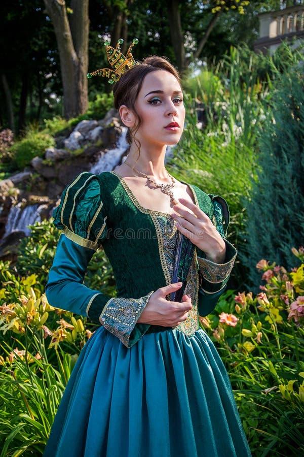 Eine Frau wie eine Prinzessin in einem Weinlesekleid im feenhaften Park stockfotos