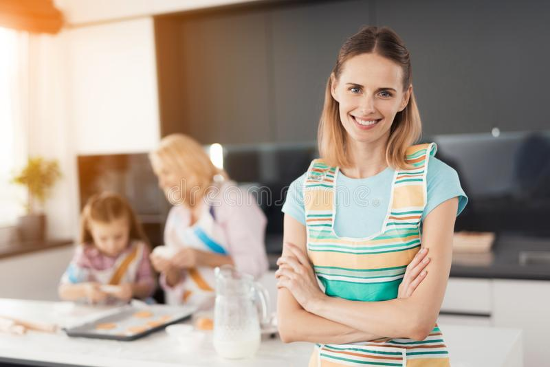 Eine Frau wirft in ihrer Küche auf Hinter ihr, ihrer Mutter und ihrer Tochter Sie sind bemüht sich vorzubereiten selbst gemachte  lizenzfreie stockfotografie