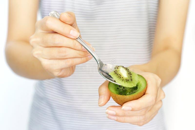 Eine Frauengriffkiwi und -scheibe mit Löffel für das Essen auf lokalisiertem weißem Hintergrund Konzept von Nahrung, gesund, Schö lizenzfreies stockfoto