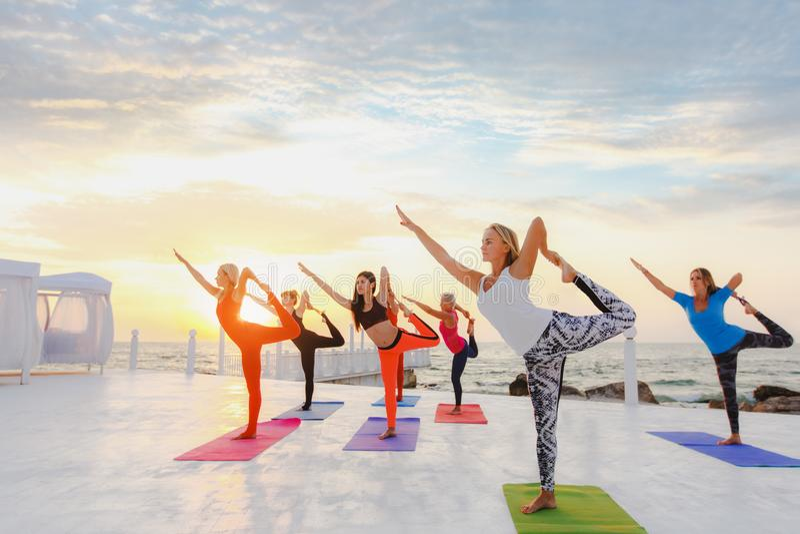 Eine Frauengruppe, die Yoga bei Sonnenaufgang nahe dem Meer tut stockbilder