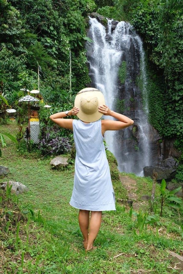 Eine Frauenstellung und Bewundern des wilden Wasserfall- und Dschungelwaldes, Bali stockfotografie