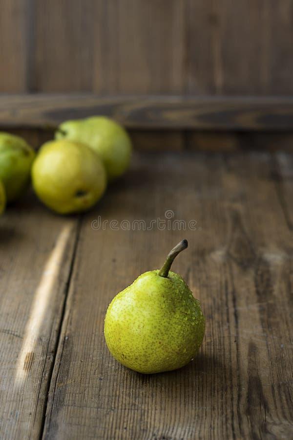 Eine frische reife organische gelbe Birne auf rustikaler hölzerner brauner Tabelle mit defocused Birnen auf Hintergrund Selektive lizenzfreie stockfotografie