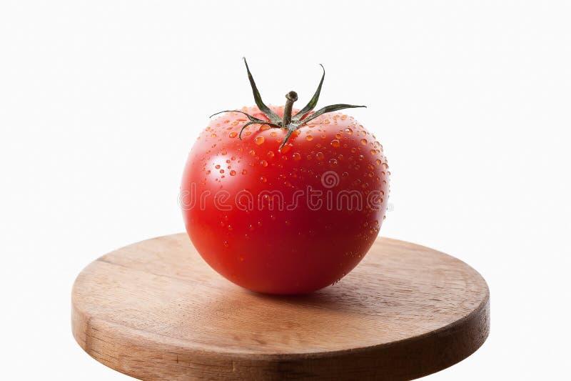 Eine frische rote Tomate auf Holztisch mit weißem Hintergrund lizenzfreies stockfoto