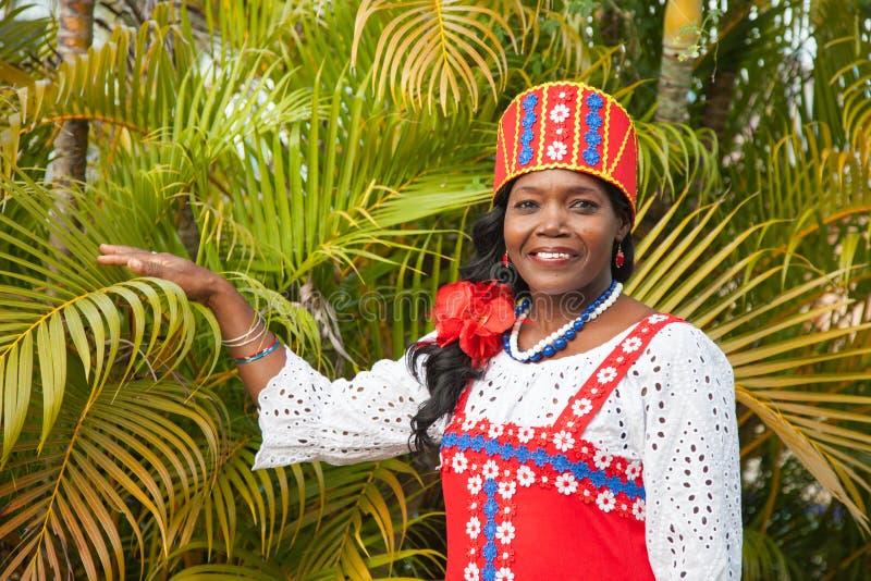Eine frohe Afroamerikanerfrau in einem hellen bunten nationalen russischen Kleid wirft im Garten vor dem hintergrund des beautifu stockfotos