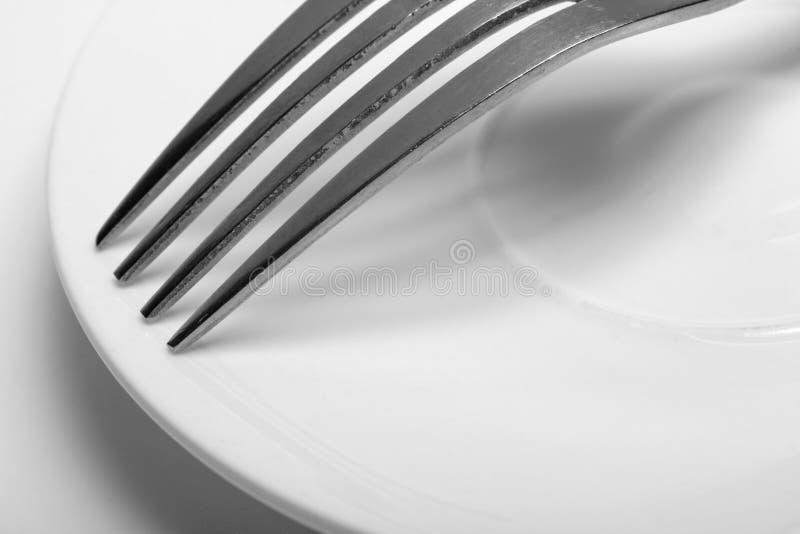 Eine Gabel auf einem Teller Nahaufnahme auf weißem Hintergrund lizenzfreies stockfoto